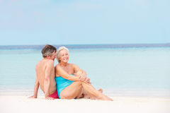 Senior Couple Relaxing On Beautiful Beach Together. Smiling Royalty Free Stock Photography