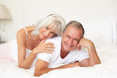 Senior Couple Relaxing On Bed Stock Photography
