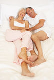 Senior Couple Relaxing On Bed Royalty Free Stock Image