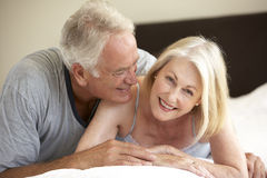 Senior Couple Relaxing On Bed Stock Photos