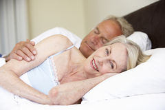 Senior Couple Relaxing On Bed Royalty Free Stock Images