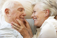 Senior Couple Relaxing In Bed Stock Image