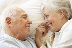 Senior Couple Relaxing In Bed Royalty Free Stock Photos