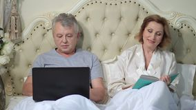 Senior couple relaxing in bed with laptop and book stock video footage