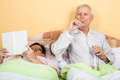 Senior couple relaxing in bed Stock Photos