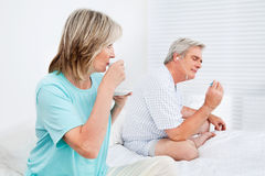 Senior couple relaxing in bedroom royalty free stock photography