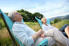 Senior couple relaxing on camping chairs Stock Images