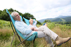 Senior couple relaxing in camping chairs Royalty Free Stock Images