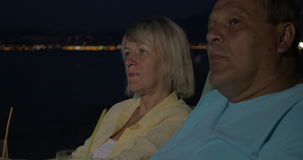 Senior couple relaxing with cocktails on beach at night stock video footage