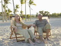 Senior Couple Relaxing On Deckchairs At Beach Royalty Free Stock Images
