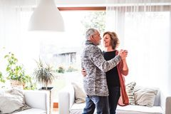 Senior couple relaxing at home, dancing. royalty free stock images