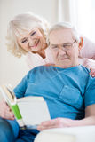 Senior couple relaxing at home, man reading book. Happy senior couple relaxing at home, men reading book Stock Images