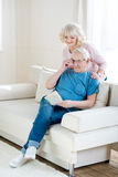 Senior couple relaxing at home, man reading book. Happy senior couple relaxing at home, men reading book Stock Photos