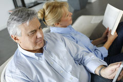Senior couple relaxing at home reading Royalty Free Stock Photo