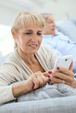 Senior couple relaxing at home with smartphone and book Stock Images