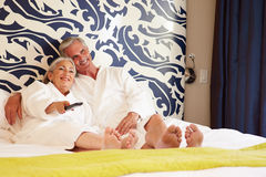 Senior Couple Relaxing In Hotel Room Watching Television Royalty Free Stock Photography