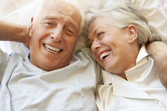 Senior Couple Relaxing In Bed Stock Images