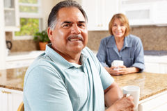 Senior couple relaxing in kitchen Royalty Free Stock Photos