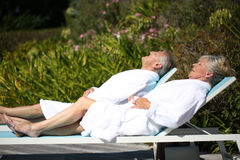 Senior couple relaxing on long chairs Royalty Free Stock Photos
