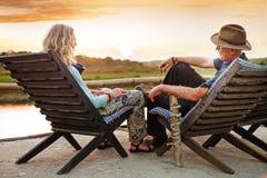 Senior couple relaxing near the lake. Senior couple enjoying a lake view sitting on chairs Royalty Free Stock Images