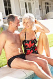 Senior Couple Relaxing by Outdoor Pool. Smiling Royalty Free Stock Photos