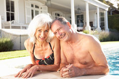 Senior Couple Relaxing by Outdoor Pool. Smiling Stock Photo