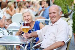 Senior couple relaxing on outdoors cafe. Happy couple of seniors, a men and his wife, are enjoying glass refreshing drink sitting at the open air terrace of cozy Royalty Free Stock Image