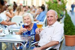 Senior couple relaxing on outdoors cafe. Happy couple of seniors, a men and his wife, are enjoying glass refreshing drink sitting at the open air terrace of cozy Stock Photography