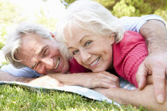Senior Couple Relaxing In Park Together Stock Photo