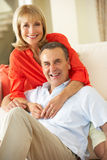 Senior Couple Relaxing On Sofa At Home Stock Images