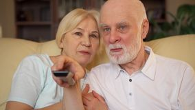 Senior couple relaxing on sofa at home watching TV. Pensioners watching channels with remote control. Senior couple relaxing on sofa at home. Happy family stock video