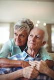 Senior couple relaxing on sofa in living room Royalty Free Stock Photos