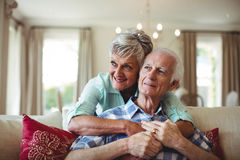 Senior couple relaxing on sofa in living room Stock Photos