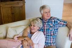 Senior couple relaxing on sofa in living room Royalty Free Stock Photography