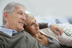 Senior couple relaxing on sofa Stock Photos