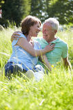 Senior Couple Relaxing In Summer Field Together Royalty Free Stock Image