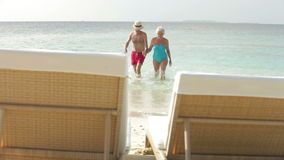 Senior Couple Relaxing On Sun Loungers stock footage