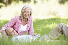 Senior Couple Relaxing In Sunny Summer Field Stock Images