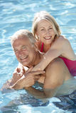 Senior Couple Relaxing In Swimming Pool Together Stock Photo