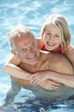 Senior Couple Relaxing In Swimming Pool Together Royalty Free Stock Photo