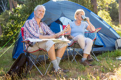 Senior couple relaxing beside their tent Stock Images