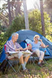 Senior couple relaxing beside their tent Stock Photography