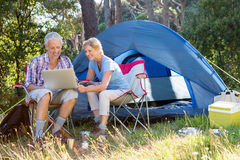 Senior couple relaxing beside their tent Royalty Free Stock Images