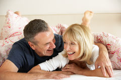 Senior Couple Relaxing Together In Bed Royalty Free Stock Image