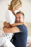 Senior Couple Relaxing Together In Bed Stock Photography