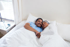 Senior couple relaxing together on bed in bedroom Royalty Free Stock Photos
