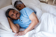 Senior couple relaxing together on bed in bedroom Stock Images