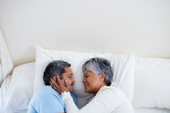 Senior couple relaxing together on bed in bedroom Royalty Free Stock Photography