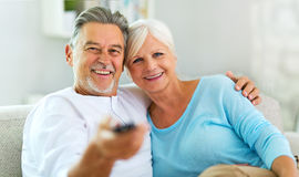 Senior couple with remote control. Senior couple at home, smiling Royalty Free Stock Images