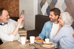 Senior couple resting in the cafe with their adult grandson. Express your emotions. Cheerful senor couple sitting at the table and talking photos with their Royalty Free Stock Photo
